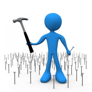 Overwhelmed Blue Person Holding A Hammer And Nail While Standing In A Patch Of Many Nails Clipart Illustration Image